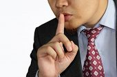 male businessman finger mouth shh gesture