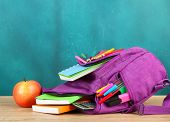 stock photo of knapsack  - Purple backpack with school supplies on wooden table on green desk background - JPG
