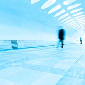 Motion blurred passenger walking in subway station.