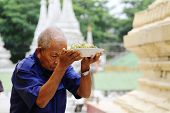 Burmese man praying and offering foods for the Gods in the Swedagon