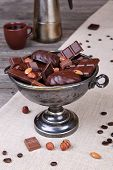 Chocolate in a metal vase on a background of gray canvas and wood