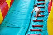 picture of inflatable slide  - Little boy playing on an inflatable playground he climbs the stairs up the stairs - JPG
