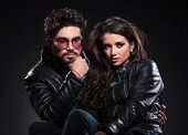 serious fashion couple in leather jackets looking at the camera