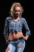 portrait of a young casual blonde in jeans and shirt standing with hands on hips