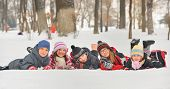 stock photo of sisters  - Group of children playing on snow in winter time - JPG