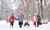 stock photo of family ski vacation  - group of children and adult playing on snow in winter time young girl pulling sister through snow on sled - JPG