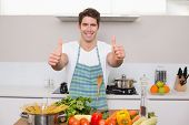 Portrait of a smiling young man with vegetables gesturing thumbs up in the kitchen at home