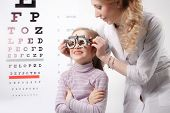 stock photo of pediatric  - Young girl smiling while undergoing eye test with phoropter - JPG