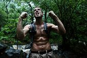 Survival man strong cheering in jungle rainforest. Muscular male survivor celebrating cheerful in fo