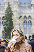 woman drinking hot wine at Christmas market, Vienna, Austria