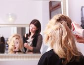 Surprised Girl With Blond Wavy Hair By Hairdresser In Beauty Salon