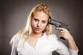 woman shooting herself with a gun on gray background