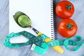 Notebook with measuring tape and vegetables on wooden background