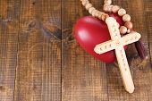 Heart with rosary beads on wooden background