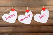 Happy Mothers Day message written on paper hearts on brown background
