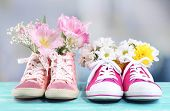 Beautiful gumshoes with flowers inside on wooden table, on bright background