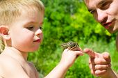 Father and son with a frog