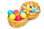 Two baked basket with Easter colored eggs and paper flowers