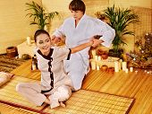 Male masseur doing massage young woman in bamboo spa.