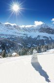 White forest, blue sky, sun and snowman in Swiss Alps during a beautiful sunny day, Klewenalp ski re