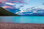Beautiful dramatic sunset over the incredibly blue lake Tekapo with mountains, Southern Alps, on the