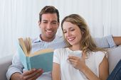 Relaxed young couple reading book on couch at home