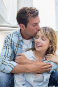 Loving young man embracing and kissing woman at home