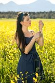 Beautiful Young Woman In A Yellow Rapeseed Field