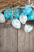 Easter eggs nest over wooden background with copy space