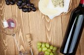 Red wine, cheese and grape on wooden table background with copy space