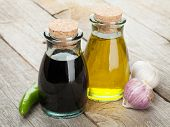 Olive oil and vinegar bottles with spices over wooden table background