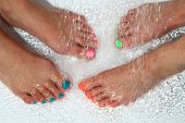 Woman Feet With Color Nails In Water