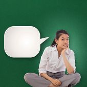 Businesswoman sitting cross legged thinking against speech bubble