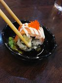 Using Chopsticks To Pinch Salmon Roll On Sauce And Wasabi
