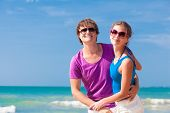 portrait of happy young couple in sunglasses having fun on tropical beach
