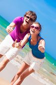 Portrait of happy young couple in sunglasses having fun on tropical beach. Thumbs up