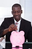 Businessman Inserting Coin In Piggybank