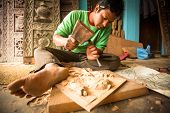 BHAKTAPUR, NEPAL - DEC 19, 2013: Unidentified Nepalese man working in the his wood workshop. More 10