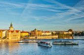 Vltava river with tourist boats and Prague Stare Mesto embankment view from Charles bridge on sunset