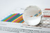 Glass globe on financial sheet