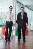 Two business men holding paper bags in modern office posing