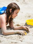 Kid girl playing with white beach sand in summer vacation
