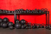 Kettlebell dumbbell and weighted slam balls weight training equipment at gym red walls