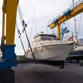 Boat wheel crane elevating motorboat to yearly paint task