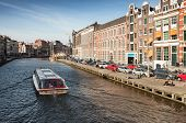 Sightseeing pleasure boat goes through the canal in historical center of Amsterdam