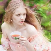 stock photo of caged  - Beautiful woman with flowering tree drinking tea - JPG