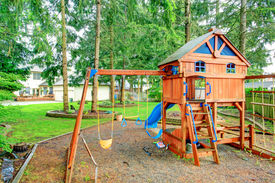 stock photo of chute  - Beautiful playground with swings chute and small cute house with stairs - JPG