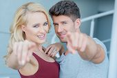Smiling attractive couple standing arm in arm pointing at the camera with focus to their faces