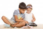 Older brother teaches younger sister play on a tablet PC. Children six and two years.