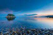 small idyllic green isle at stoney coast in italy while sunrise